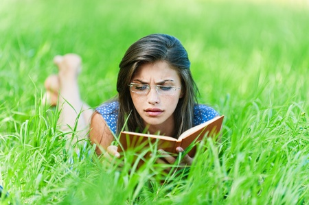 portrait of young sad, beautiful woman with glasses lying on the grass reading book photo