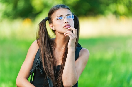 tailings: pretty young woman dreams of wearing glasses on the background of summer green meadow