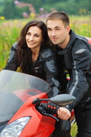 man machine: portrait young man beautiful couple man woman sitting motorcycle background summer green field Stock Photo