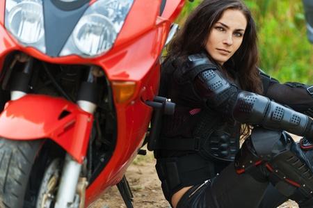 casco moto: Retrato de una mujer joven y bella pensativo sentado cuero chaqueta de moto inclinada