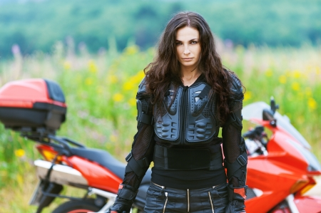 portrait beautiful sad dark-haired woman leather jacket standing alongside red motorcycle background summer green field photo