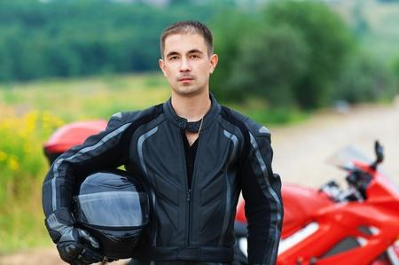 motociclista: retrato de joven agradable casco de motocicleta triste hombre mano que sostiene al lado de la motocicleta de fondo verde bosque de verano