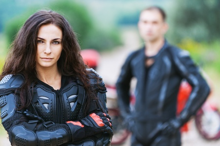 portrait beautiful long-haired woman serious leather jacket gloves background biker guy photo