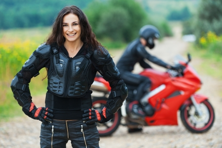 Beautiful long-haired skinny woman standing background guy riding motorcycle road photo