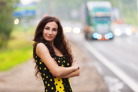 Portrait beautiful young long-haired woman background road cars photo