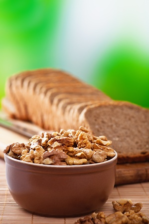 purified kernels walnuts in bowl,cutting board cut rye bread ,knife background wooden table and green photo
