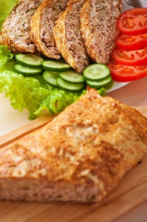 slices of savory meatloaf with vegetables cucumbers and tomatoes, lettuce, close-up photo