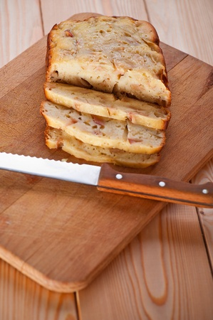 freshly baked charlotte closeup sliced muffin slices, near sharp knife for cutting bread on wooden cutting board photo