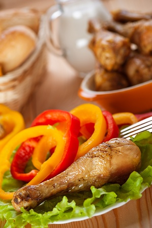 dish of fried chicken drumsticks delicious on lettuce leaves with sliced circles of Bulgarian pepper in background transparent glass jug with milk and wicker vase with bread photo