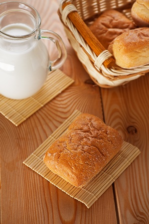 on wooden table pone bun, pitcher of milk,on wooden background photo