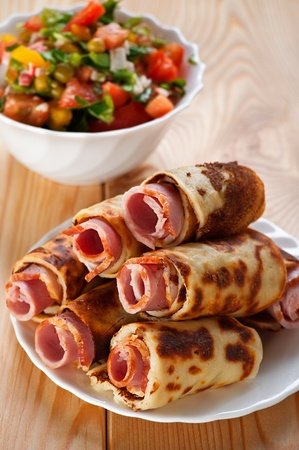 on wooden background, meat rolls (bacon, ham, ham) in the omelet, vegetable salad (cucumbers, tomatoes, parsley) Imagens