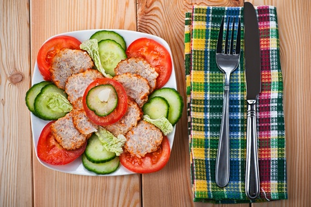 close-up of variety of delicious foods, chopped vegetables (cucumbers, tomatoes), slices of meatloaf, wooden kitchen table with napkin, fork photo