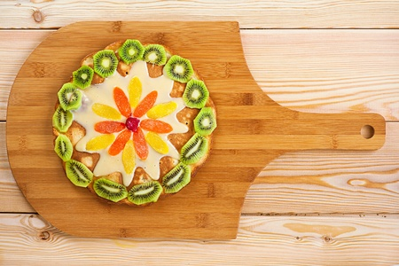Cake with kiwi and pineapple slices and cream on wooden board. photo