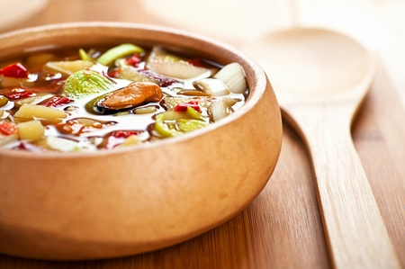 Thai Tom Yam soup with seafood in a wooden bowl on the table. photo