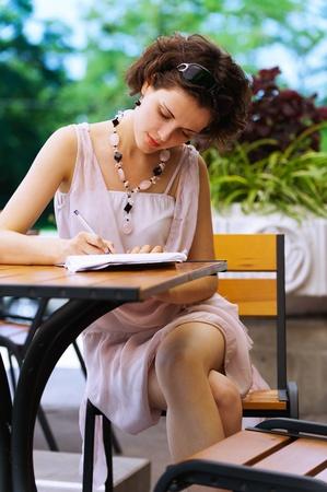 buiten portret van mooie krullende jonge vrouw zit in het park cafe tafel en witte pen in schrijven-boek Stockfoto