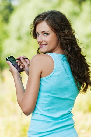 touch screen phone: Portrait of young attractive brunette woman wearing blue t-shirt, working with smartphone and stylus at summer green park.