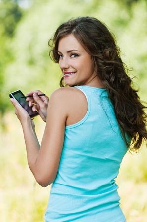 Portret van jonge aantrekkelijke brunette vrouw gekleed in een blauwe t-shirt, het werken met smartphone en stylus in de zomer groen park.