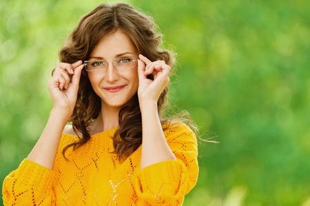 Portret van mooie brunette jonge vrouw die brillen en gele blouse, die zich op de zomer groen park.