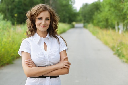 Portrait of beautiful young brunette woman wearing white blouse at summer green park. Stock Photo - 11937609