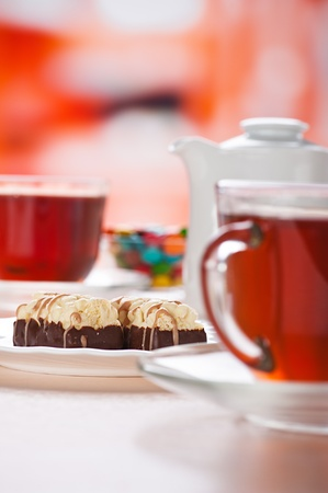 two clear glass cups with black tea, chocolate cake two and colorful candy-coated in deep bowl and white ceramic teapot on the kitchen table, all the products on red background photo
