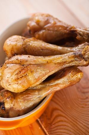 pollo a la plancha: cuatro baquetas pollo frito sabroso plato en amarillo en la mesa de madera Foto de archivo