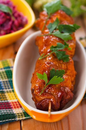 against the background of the wooden kitchen table on checkered cloth, mouth-watering meat kebab (pork, beef, lamb, chicken) on skewer in large bowl Stock Photo