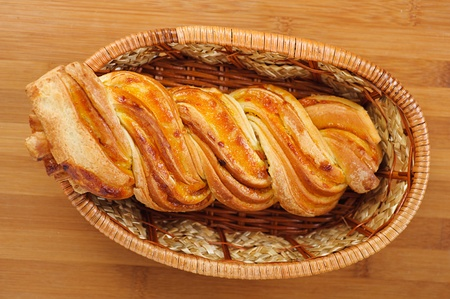Bread twirl in the basket on a wooden table. photo