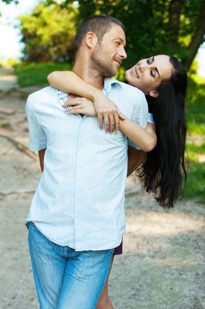 beloved: Two beloved against summer green park. Girl has put hands on shoulders of beloved and smiles. Stock Photo