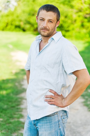 courageous: Portrait of young beautiful unshaven man in light shirt against summer green park. Stock Photo