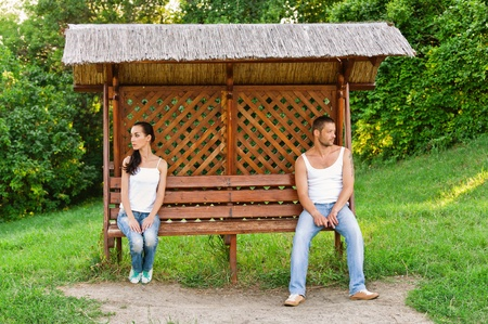 swearing: Young woman and young man sitting on opposite sides of bench in city park because they had falling out. Stock Photo