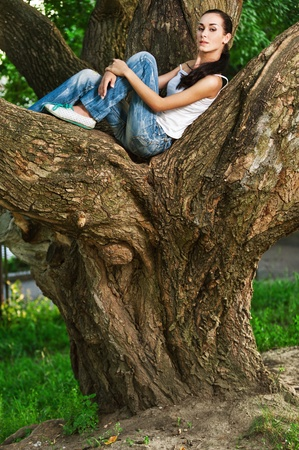 girl sit: Beautiful young dark-haired woman sits on huge tree in city park.