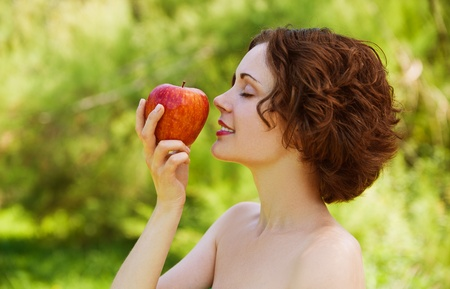 eyes shut: outside portrait of beautiful young curly woman with eyes shut with red apple in park