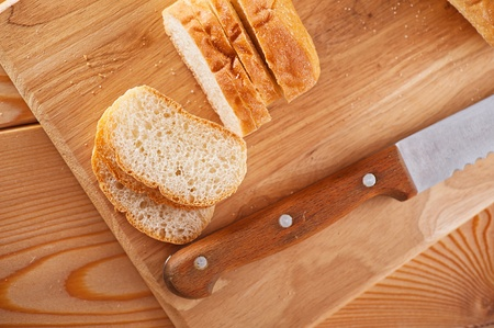 Close-up sliced bread (long loaf) on cutting wooden board, knife Stock Photo - 12020731