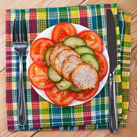meatloaf: close-up of variety of delicious foods, chopped vegetables (cucumbers, tomatoes), slices of meatloaf, wooden kitchen table with napkin, fork Stock Photo