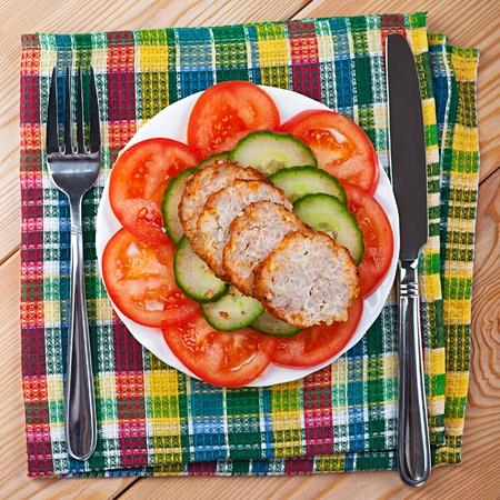 albondigas: primer plano de la variedad de deliciosas comidas, verduras picadas (pepinos, tomates), rebanadas de pastel de carne, mesa de cocina de madera con la servilleta, tenedor Foto de archivo