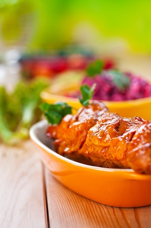against the background of the wooden kitchen table on checkered cloth, mouth-watering meat kebab (pork, beef, lamb, chicken) on skewer in large bowl photo