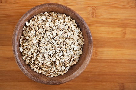 Plate with raw oatmeal on wooden table. Stock Photo - 12020734