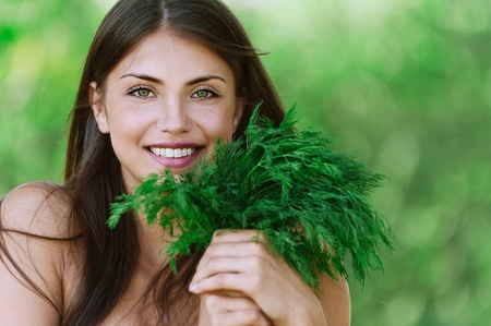 greens: portrait beautiful young woman smiling holding bunch green dill background summer green park