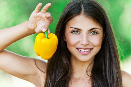 Portrait of young smiling fair-haired woman holding Bulgarian pepper and looking somewhere at summer green park. Stock Photo