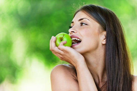 sidewards: portrait young charming brunette woman biting green apple background summer park