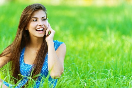 Young beautiful woman in blue dress sitting on grass in summer city park and talking on cell phone.