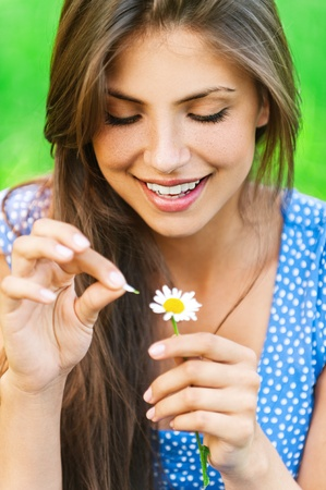 fortunetelling: Young lovely smiling woman wonders on flower, tearing petals, close-up. Stock Photo