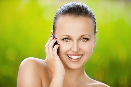 Beautiful young woman talking at the cell phone at summer green park Stock Photo - 12472539