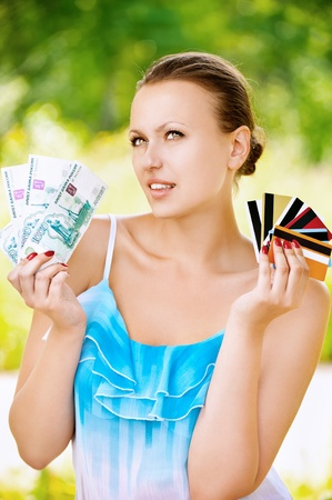 Portrait of young pretty woman holding credit cards and cash at summer green park photo
