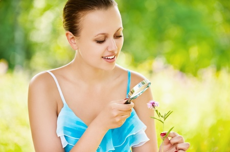 Young pretty smiling woman examining with a magnifying glass flower at summer green park photo