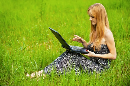 Young beautiful woman working on laptop at summer green park Stock Photo - 12472656