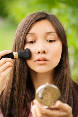 Portrait of young beautiful asian girl looks powder mirror at summer green park Stock Photo - 12472760