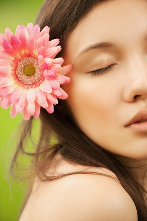 Closeup portrait of attractive asian brunette young woman with pink flower in hair Stock Photo - 12472665