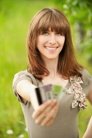 Portrait of smiling young woman holding several credit cards at summer green park photo