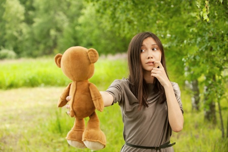 Portrait of pretty young woman holding teddy bear at summer green park photo